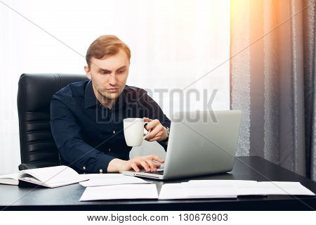 Casual dressed man working on laptop at home.