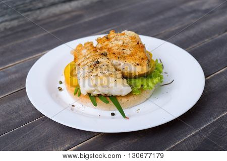 Fishburger with pepper and lettuce on the plate