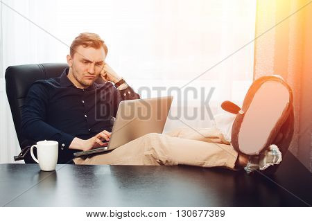 Pensive businessman with legs on the desk and laptop on knees.