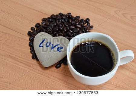 heart rock with black coffee cup and seed