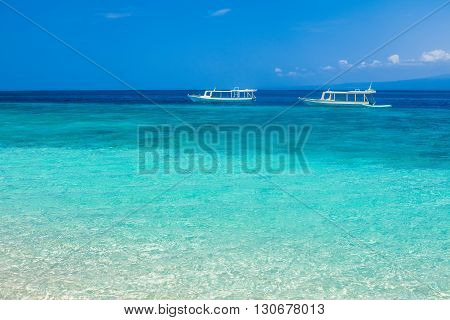 Beautiful beach and tropical turquoise sea with boats on horizon. Vacation