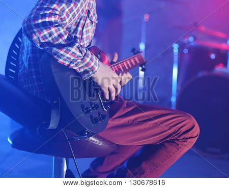 Man playing electric guitar on stage.