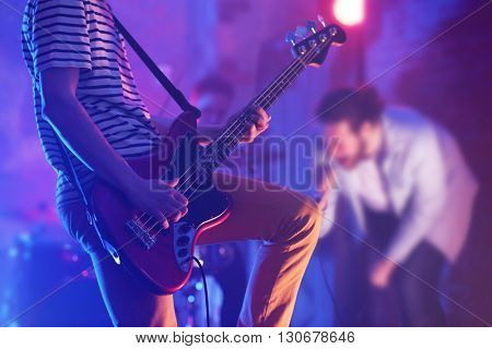 Man playing electric guitar on a stage.