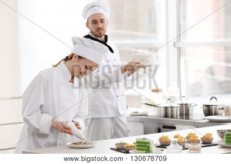 Female chef decorating cookies with chocolate.