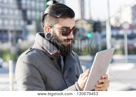 Young Hipster Businessman Consults His Laptop In The Heart Of City