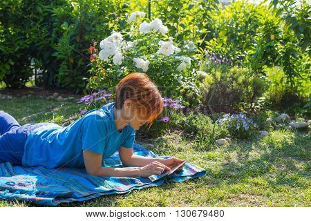Woman Working With Tablet Outdoors In Flowery Garden