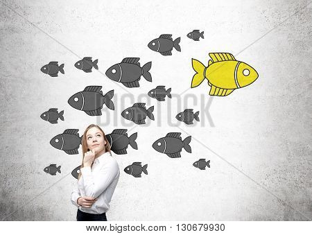 Different direction concept with thoughtful businesswoman and goldfish sketch on concrete wall