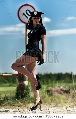 Young beautiful police woman near barrier into restricted area