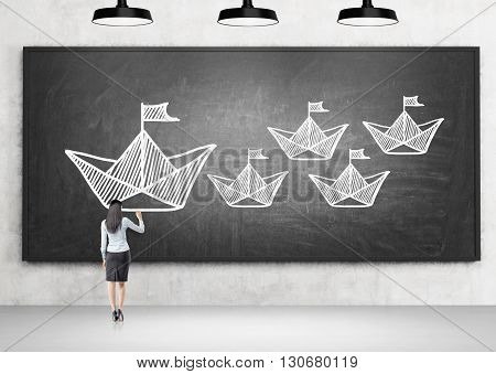 Leadership concept with businesswoman drawing large paper ship next to small ones on chalkboard hanging in concrete room with lamps