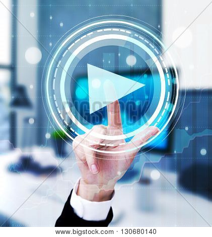 Businesswoman hand pressing abstract digital play button on blurry office background