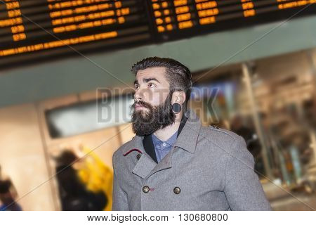 Hipster Businessman Consult The Board Of Timetable Trains