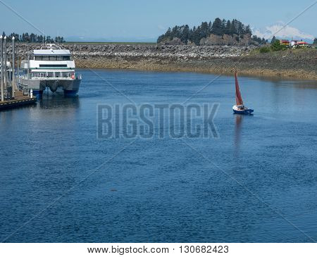 A small sailboat heads out to of a harbor on a light breeze.
