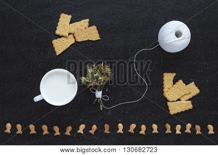 Composition with blossoming twigs, milk, a cotton skein and cookies on black background