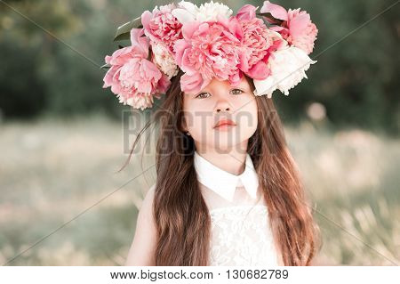 Beautiful kid girl 4-5 year old posing outdoors. Wearing peony wreath. Looking at camera.