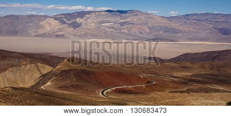 Long winding heart shaped highway descending into Death Valley against immense mountain and sandy valley