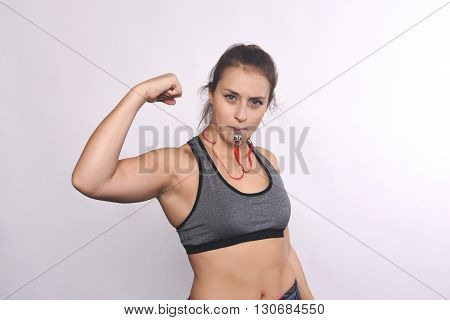 Portrait of an athlete young woman with whistle. Isolated white background.