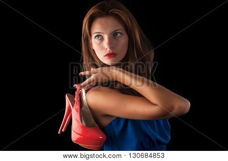 Attractive cool redhaired woman holding red shoe. Isolated over black background