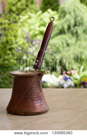 Old brown coffee pot with wooden handle on a table over green garden background with flowers