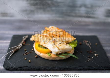 Fishburger with pepper and green onion on the bread on the stone blackboard