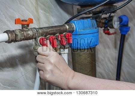 Plumbing manifold system tubing for house water distribution control valves home water pipe close-up human hand opening valve.