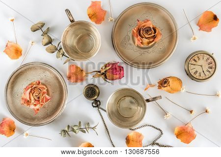 Two cups with roses and watch. Flat lay. Top view