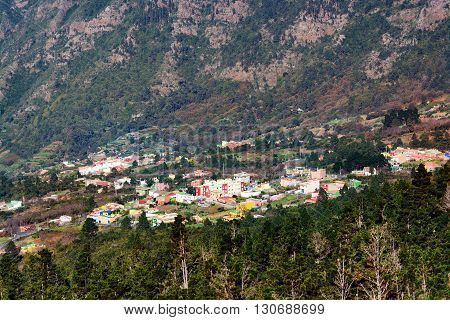 View of mountain with densely populated city with residential buildings green trees at Tenerife island, Spain