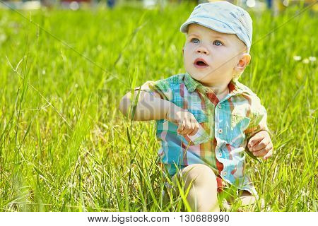 little boy sitting in the grass. baby for a walk. child summer outdoors