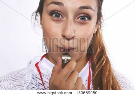 Close up of beautiful and athlete young woman with whistle. Isolated white background.