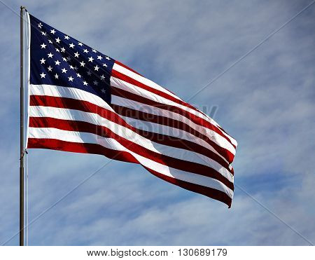 Flag Usa In Wind On Blue Sky And Clouds