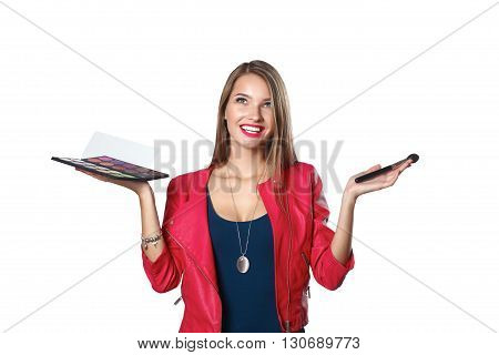 Young beautiful woman holds in one hand and a palette with paint and shadows for makeup, second hand brush for makeup.