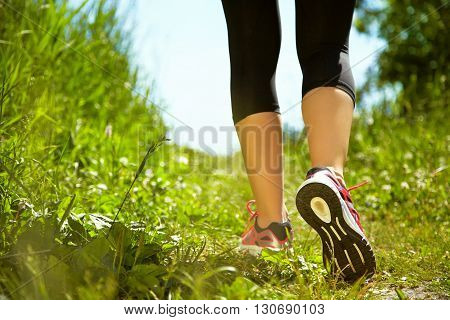 selective focus. runner feet closeup. athlete in the park outdoors. running shoes. jogging