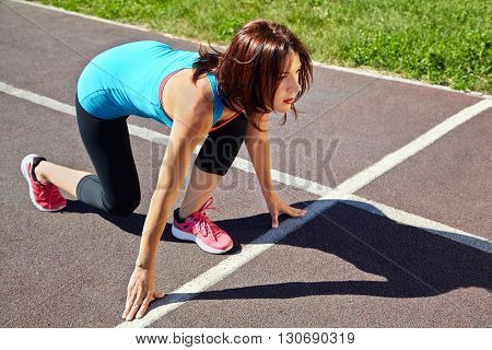 athletic woman at the starting line athlete running on jogging track at the stadium. jogging outdoors