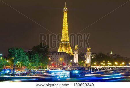 Paris; France-May 18 2016 : The Eiffel tower with night illumination and columns of Alexandre III bridge Paris France.