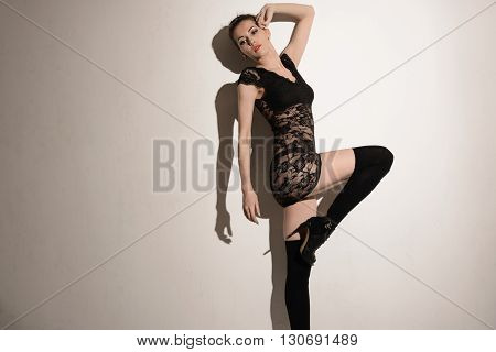 Sexy woman in black lace dress and stockings studio shot on white background