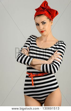 Studio portrait of a beautiful woman in sailor stripes swimsuit