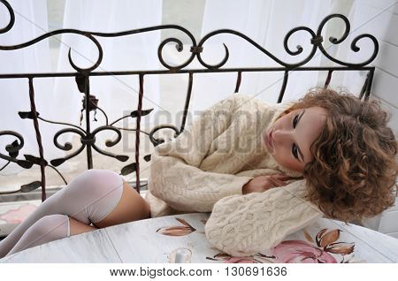 Beautiful woman with curly hair sitting at table, in warm sweater and white stockings, relaxing at outdoor