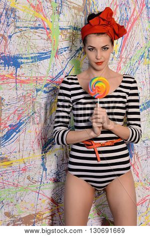 beautiful girl with big lollipop at wall with different color splash