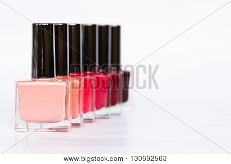 A palette of nail polish bottles on a white background