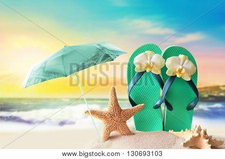 The beach umbrella. Starfish and flip flops on the sandy beach at ocean background