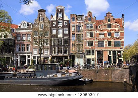AMSTERDAM, NETHERLANDS - MAY 4, 2016: Old houses of traditional architecture and ship along a canal in Jordaan neighborhood in Amsterdam, Netherlands. Amsterdam is the capital and most populous city of the Netherlands.