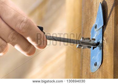 hand unlocking front door lock of house closeup