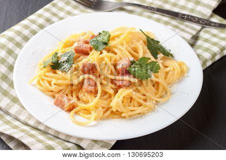 Pasta Carbonara with ham and cheese on checkered towel.