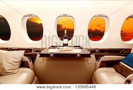 Luxury interior in bright colors of genuine leather in the business jet, sky, clouds and sunset through the porthole