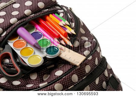 backpack with school supplies in front of white background. close-up photo