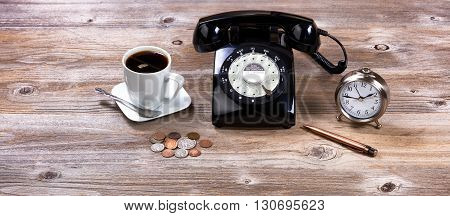 Vintage desktop with antique rotary dial telephone clock pen coins and coffee.