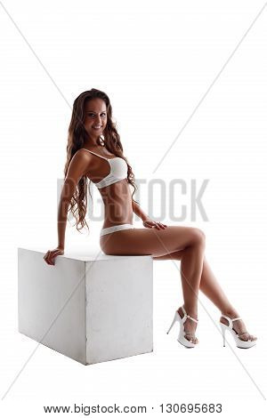 Advertising underwear. Slim tanned model sitting on cube