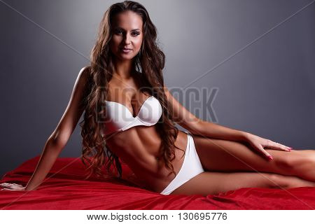 Image of long-haired underwear model posing lying in bed