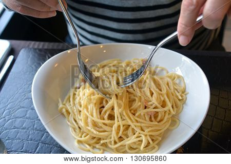 Italian spaghetti Carbonara on a white bowl on a restaurant table