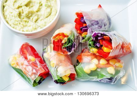 rainbow spring rolls with avocado white bean hummus on white wood background