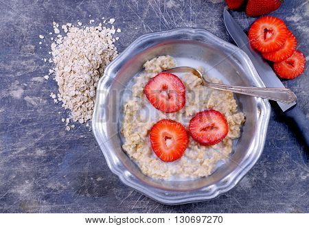 An old pewter bowl filled with oatmeal, fresh strawberries and cream sitting on a stained and scratched steel background. Fresh oats and a knife added. Overhead, flat lay perspective. Rustic vibe.